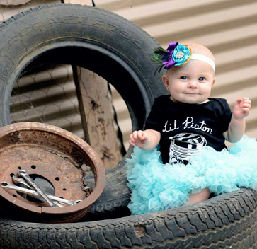 Baby in Lil Piston Shirt near tires